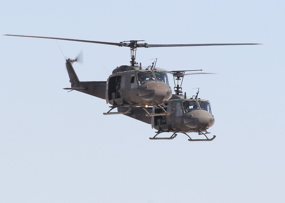 Two uh 1 iroquois helicopters in formation click here to open a new